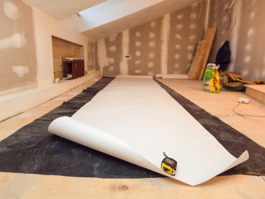 Working process of wallpapering  on the drywall in small room apartment is under construction, remodeling, renovation, extension, restoration and reconstruction. Paperhangings is measured by tape-measure on the floor and cut. Concept of home improvement